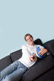 Happy young man watching sport on tv Stock Photo