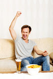 Happy young man watching sports on TV Stock Photography