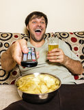 Happy young man watching television, eating potato chips and dri Stock Photography
