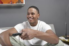 Happy Young Man Watching TV. Happy young African American men watching TV Stock Image