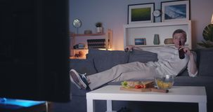 Happy young man watching TV drinking beer relaxing on couch at night stock footage