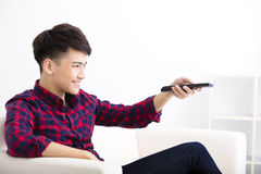 Happy Young man watching tv on the sofa Stock Images