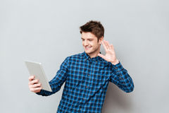 Happy young man waving to friends by tablet computer. Image of happy young man standing over grey wall and talking with friends by tablet computer while waving Royalty Free Stock Image