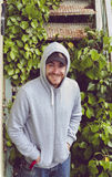 Happy young man wearing a hoodie and a baseball cap Royalty Free Stock Photos