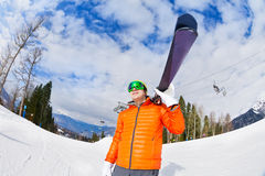 Happy young man wearing mask holds ski in winter Royalty Free Stock Images