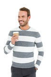 Happy young man in winter wear holding disposable coffee cup Royalty Free Stock Photo