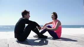 Happy young man and woman high fives sitting near the beach. Waves splashing agains the rocks. Young couple high five stock video