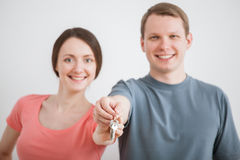 Happy young man and woman holding a bunch of keys. Happy young men and women holding a bunch of keys, neutral background Stock Photo