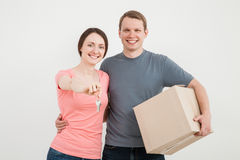 Happy young man and woman holding cardboard box and keys Stock Photos