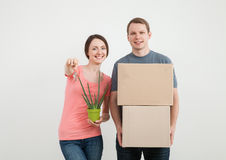 Happy young man and woman holding cardboard box and keys Royalty Free Stock Image