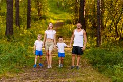 Happy young man and woman holding two children`s hands in summer outdoors. Happy family in white t-shirts. In the woods stock photo