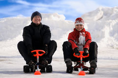 Happy young man and woman riding snowmobiles Stock Image