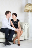 Happy young man and woman sit at sofa and look at each other Royalty Free Stock Images