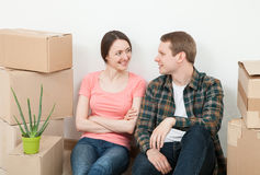 Happy young man and woman sitting near  cardboard boxes Royalty Free Stock Images