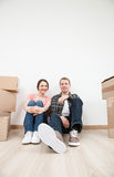 Happy young man and woman sitting near  cardboard boxes Stock Photo