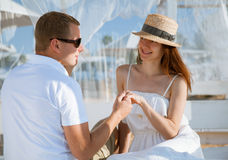 Happy young man and woman sitting under a white baldachin Royalty Free Stock Photos