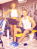 Happy young man and woman taking pause between exercising in gym Royalty Free Stock Image