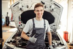 A happy young man is at work. Car service and maintenance royalty free stock photography