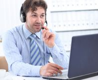 Happy young man working at callcenter, using headset. Photo with copy space Royalty Free Stock Images