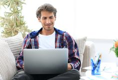 Happy winner. Young excited man using laptop computer while sitting on sofa. royalty free stock photos