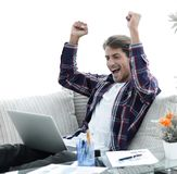 Happy winner. Young excited man using laptop computer while sitting on sofa. Happy young man working with laptop from home. photo with copy space Stock Images