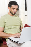 Happy Young Man Working on Laptop at Home Royalty Free Stock Images