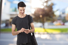 Happy young man writing message on mobile phone Royalty Free Stock Images