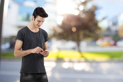 Happy young man writing message on mobile phone Stock Photo