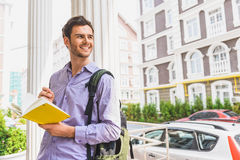 Happy young man writing into notebook Royalty Free Stock Photo
