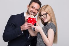 Happy young managers drop bitcoin into piggy bank stock photo