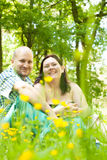 Happy young married couple between flowers. Happy young couple is sitting in a field of buttercups Stock Photos