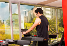 Happy young men doing some jogging on a treadmill at the gym. Happy young man doing some jogging on a treadmill at the gym Stock Image