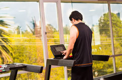 Happy young men doing some jogging on a treadmill at the gym. Happy young man doing some jogging on a treadmill at the gym Royalty Free Stock Image