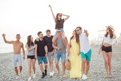 Group of Friends Walking at Beach, having fun, womans piggyback on mans, funny vacation. Happy young men giving their girlfriends piggyback walks at beach. Group royalty free stock images