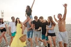 Group of Friends Walking at Beach, having fun, womans piggyback on mans, funny vacation. Happy young men giving their girlfriends piggyback walks at beach. Group stock photos