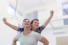 Handsome man piggybacking his girlfriend. Happy young men piggybacking his girlfriend at home Stock Photo