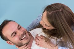 Young man piggybacking his girlfriend. Happy young men piggybacking his girlfriend isolated on blue background Royalty Free Stock Image