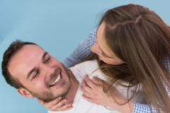 Young man piggybacking his girlfriend. Happy young men piggybacking his girlfriend isolated on blue background Stock Photos