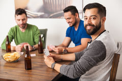Happy young men playing cards at home royalty free stock photography