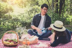 Happy Young man playing the guitar or Ukulele and Singing Song w. Happy Young men playing the guitar or Ukulele and Singing Song with couple love sitting on red Royalty Free Stock Image
