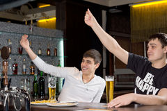 Happy young men signalling for service. Raising their arms in the air as they sit together at the counter in a bar drinking beer stock photos