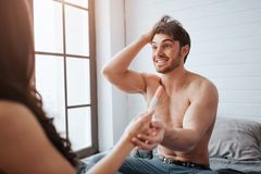 Happy young man smiling to woman. They sit on bed in room at window. Guy cheering. He hold woman`s hand with positive stock images