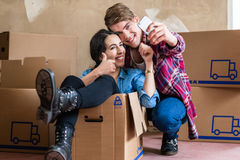 Happy young man and woman making a selfie after moving in into a stock photography