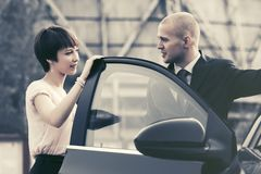 Happy young couple talking beside a car Stock Image