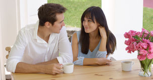 Happy young mixed couple sitting at table Royalty Free Stock Image
