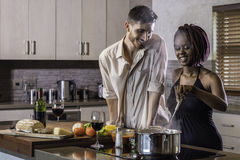 Happy young mixed race couple cooking dinner in kitchen Stock Images