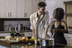 Happy young mixed race couple cooking dinner in kitchen Royalty Free Stock Photo