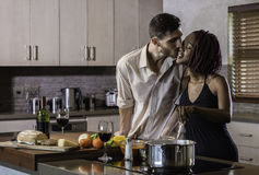 Happy young mixed race couple cooking dinner in kitchen Stock Image