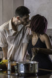Happy young mixed race couple cooking dinner in kitchen Royalty Free Stock Photos