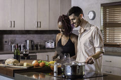 Happy young mixed race couple cooking dinner preparing food in the kitchen Royalty Free Stock Images